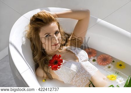 A Young Beautiful Woman In Lacy White Underwear Lies In A Milk Bath With Flowers, Enjoying A Rest. B