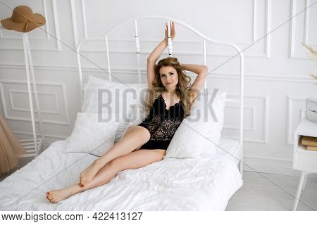 A Sexy Young Slender Woman In Black Underwear Is Lying In Bed With Her Hands Behind The Metal Headbo
