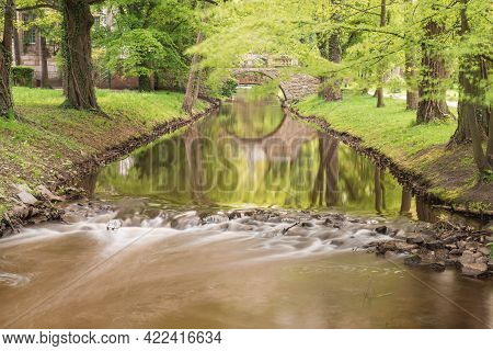Manor Park In The City Of Ilowa In Poland. A Stone, Small, Arched Pedestrian Bridge Over The Czerna