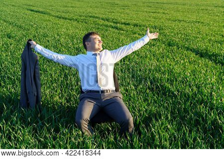businessman sits in an office chair in a field and rests, freelance and business concept, green grass and blue sky as background