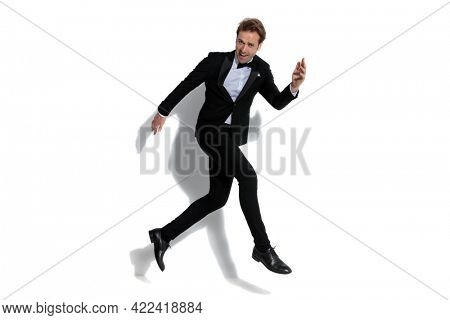 sexy businessman full of joy is jumping in the air against white studio background