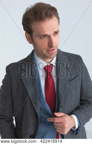 portrait of a classy businessman fixing his suit, wearing a coat and looking away