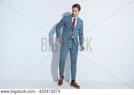 full body picture of happy young businessman in blue suit holding hand in pocket and looking to side while smiling and walking on grey background in studio