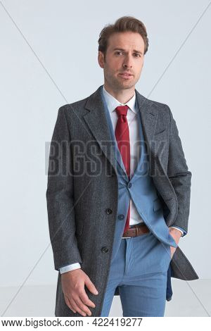 handsome businessman sticking one hand in pocket, posing with attitude and wearing a nice suit