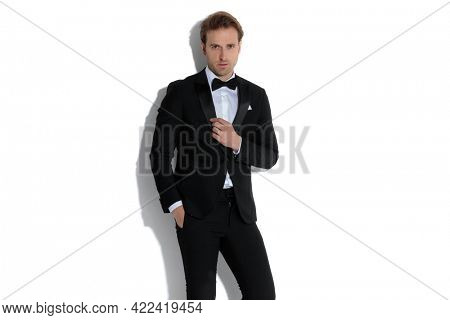 young businessman holding one hand in pocket and arranging his collar in a fashion pose