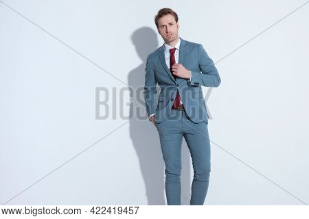 attractive unshaved businessman in blue suit holding hand in pocket and fixing tie while walking on gray background in studio