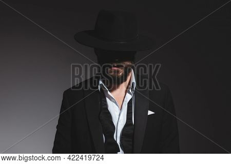 portrait of a mysterious businessman wearing a black hat, tuxedo and an undone bowtie on gray background