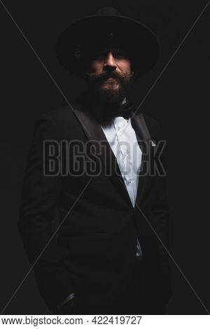 sexy fashion businessman posing with his hands in pockets and looking at the camera