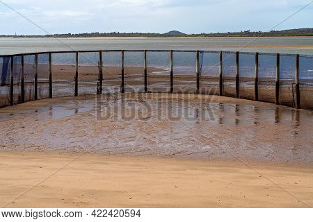 A Netted Safe Swimming Enclosure On A Beach With The Tide Out