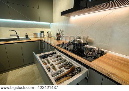 Modern large luxury dark gray kitchen, pulled out drawer with kitchen utensils