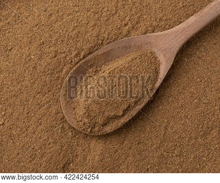 Top View, Closeup Of Ground Cumin On A Wooden Spoon. Food Backdrop.