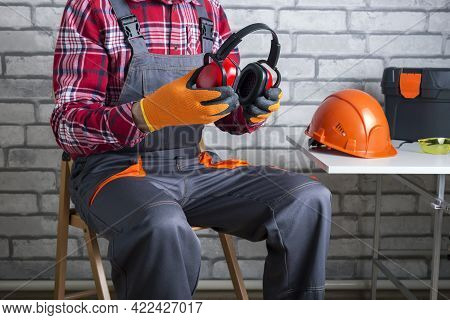Builder Puts On Personal Protective Equipment. Manual Worker Putting Protective Headphones.