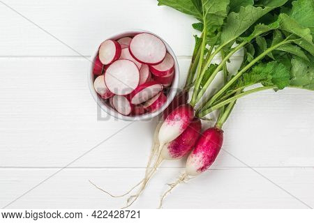 Top View Of A Bunch Of Radishes And A Bowl Of Radish Slices On A White Wooden Table. A Fresh Crop Of