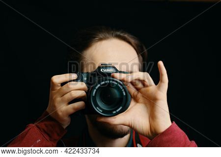 Man Takes Pictures Canon Camera And Tries To Focus The Lens. Photo Editor, Cameraman, Journalist. Bi