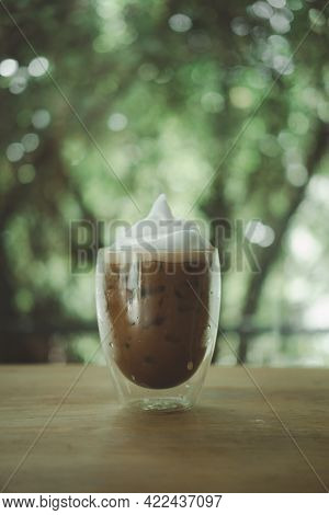 Iced Mocha Coffee With Milk Froth On Top In A Double-walled Glass Placed On Wood Table
