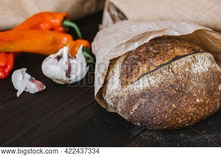 Artisan Sourdough Bread On Wooden Table With Vegetables. Freshly Baked Round Loaf Of Sourdough Bread