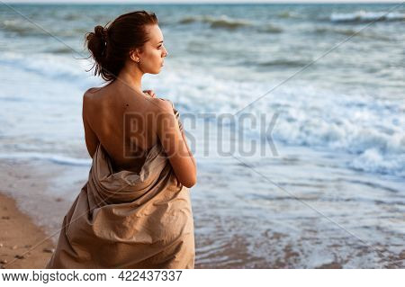 The Girl On The Seashore In The Evening Stands. Lonely Looking Into The Distance On The Beach At Sun