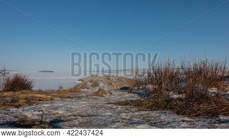 Winter Landscape. The Promontory Juts Out Into A Frozen Lake. On The Ground Covered With Snow, There