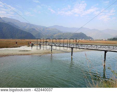 Landscape And Nepali People Walking On Katre Harpan Khola Bridge Cross Irrigation Reservoir Dam And