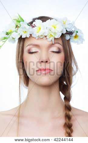 Portrait of beautiful young woman with closed eyes wearing floral wreath on her head