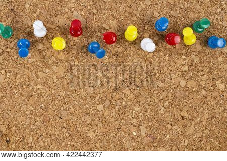 Colored Pushpins Stuck Into The Surface Of A Cork Wood Office Board, Copy Space.