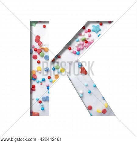 Sweet Glaze Font. The Letter K Cut Out Of Paper On The Background Of White Sweet Glaze With Colored