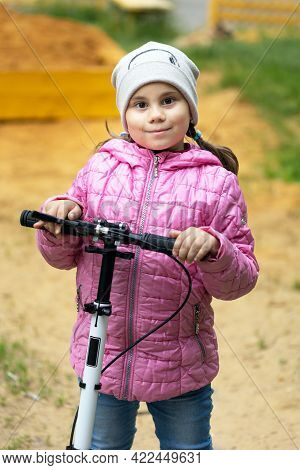Portrait Of Active Little Child Girl On A Scooter In A Park Outdoors