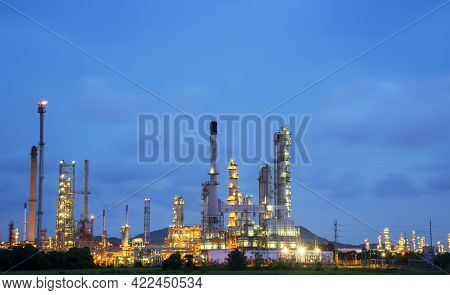 Oil Refinery Plant Chemical Factory And Power Plant With Many Storage Tanks And Pipelines At Sunset.