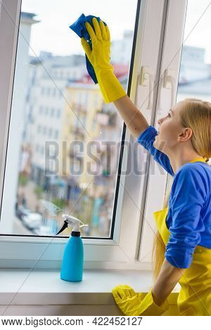 Young Woman In Yellow Gloves Cleaning Window Pane At Home With Rag And Spray Detergent. Cleaning Con