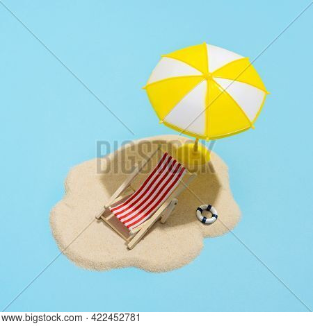 Summer concept. Sun umbrella and sun lounger on sea sand on blue background. Sun protection concept in summer.