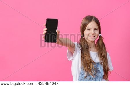 White Girl Of 10 Years Old In A White Top Holds A Black Phone On A Pink Background