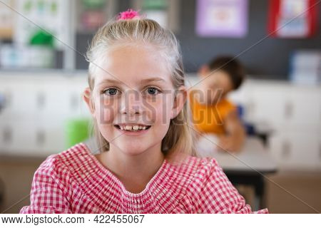 Portrait of caucasian girl smiling while sitting on her desk in the class at school. school and education concept