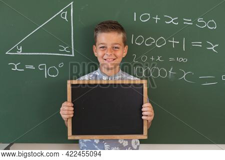 Portrait of caucasian boy at chalkboard with geometry on it, holding blank chalkboard, smiling. childhood and education at elementary school.