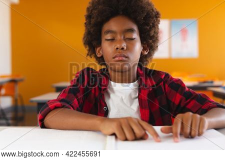 African american schoolboy sitting in classroom with eyes closed reading braille book with fingers. childhood and education at elementary school.