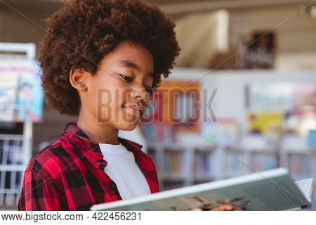 Smiling african american schoolboy reading book standing in school library. childhood and education at elementary school.