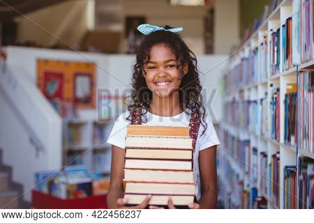 Portrait of smiling african american schoolgirl carrying stack of books in school library. childhood and education at elementary school.