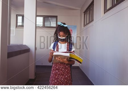 African american schoolgirl in face mask standing in school corridor reading book. childhood and education at elementary school during coronavirus covid19 pandemic.