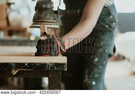 Female carpenter smoothing the lumber with a sander