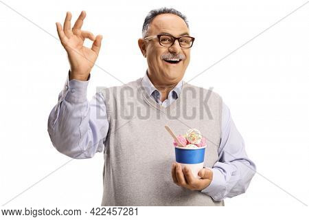 Mature man holding ice cream in a paper cup and gesturing ok sign isolated on white background