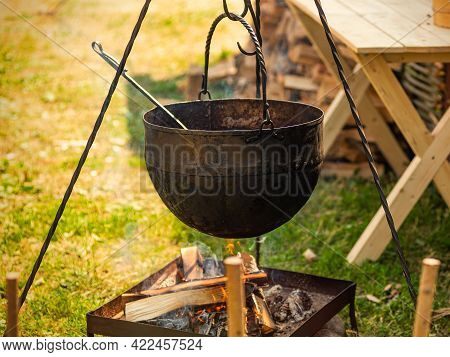 Cooking Street Food. Cooking Soup In A Cauldron On A Fire Outside.