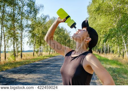 Resting Young Caucasian Woman Drinks Water From Plastic Bottle After Hard Workout Closeup. Thirst, H