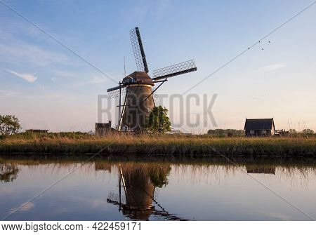 Traditional Dutch Windmill Reflected In The Water Surface Of The Canal. Outdoor Scene In Famous Dutc