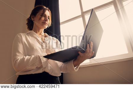 Middle-aged business woman stands in the office near the window, holding open laptop