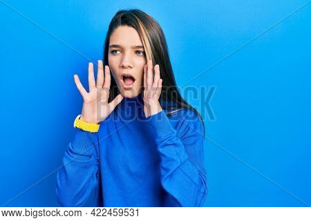 Young brunette girl wearing turtleneck sweater shouting angry out loud with hands over mouth