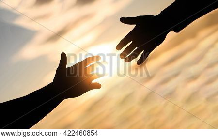 Giving A Helping Hand. Rescue, Helping Gesture Or Hands. Mercy, Two Hands Silhouette On Sky Backgrou