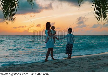 Mother And Two Kids Walking At Sunset Beach