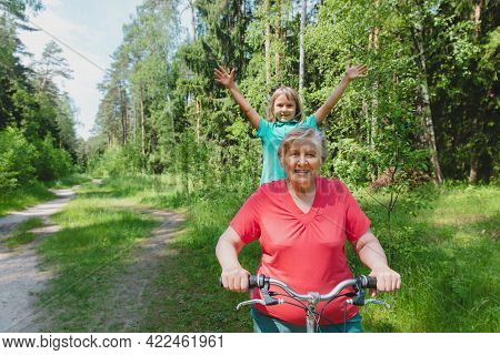 Happy Little Girl With Grandmother On Bike Ride In Nature