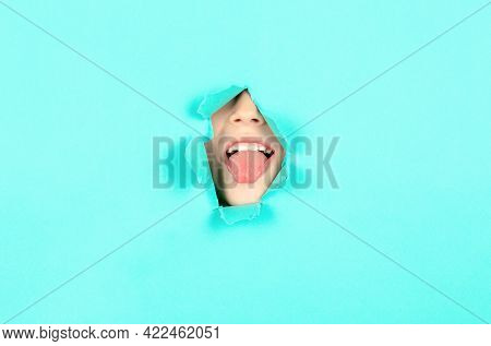 Close-up Boy Face Showing Her Tongue. Child Stuck Out Her Tongue Through A Hole In The Paper. Boy Sh