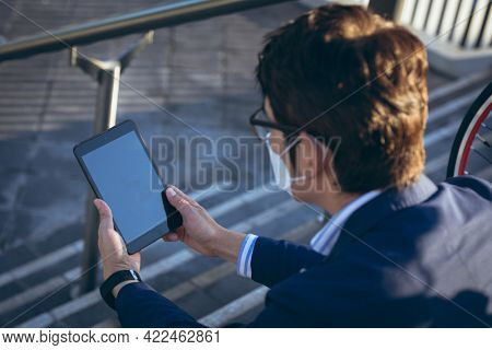 Asian businessman wearing face mask using tablet sitting on steps in city street. digital nomad out and about in city during covid 19 pandemic concept.