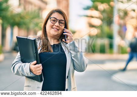 Young plus size businesswoman talking on the smartphone holding binder at the city.